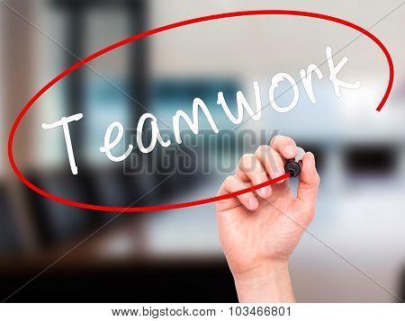 Man Hand writing Teamwork with black marker on visual screen.