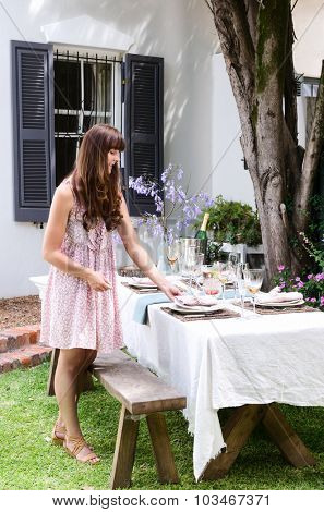 Beautiful woman lying the table, getting ready for the outdoor garden party