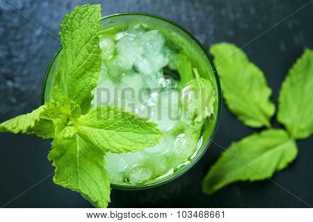 high-angle shot of a glass with an appetizing mojito garnished with a twig of mint on a black slate background