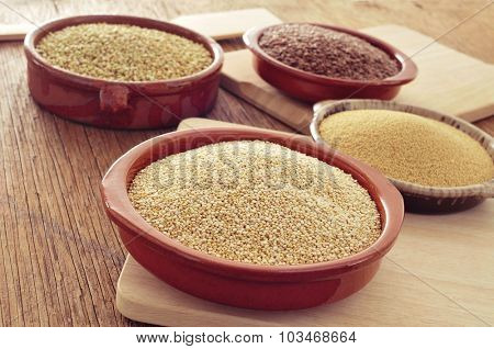 some earthenware bowls with amaranth, quinoa, brown flax and buckwheat seeds on a rustic wooden table