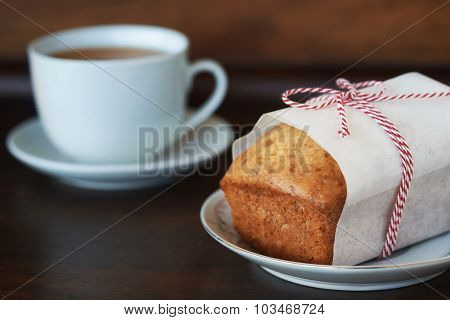 A gift wrapped loaf of banana bread with cup of tea next to it