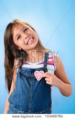 Cute young girl in denim dungarees smiling and holding pink heart shape cookies against her heart, valentines or mothers day concept