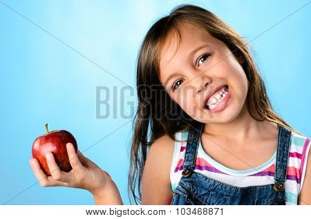 Cute young girl holding a red apple, healthy living, education concept on blue background