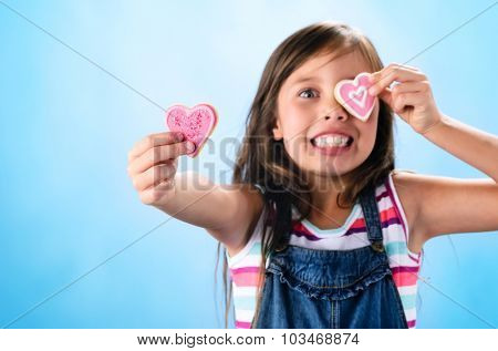 Grinning smiling young girl holds out pink heart shape cookie on blue background, selective focus on cookie valentines or mothers day concept