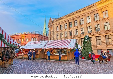 People Enjoy Christmas Market In Old Town Of Riga