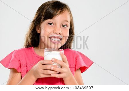 Cute young girl drinking and holding a glass of milk with a milk moustache
