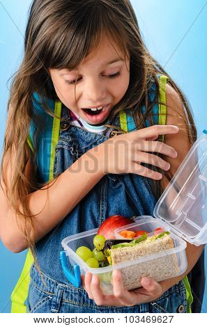 Excited young school girl holding and looking into healthy lunchbox filled with fresh fruit and sandwich on blue background