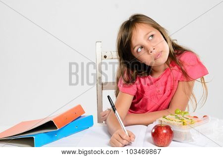 Hardworking school girl thinks and concentrates on her homework with an apple and healthy packed lunch on the table