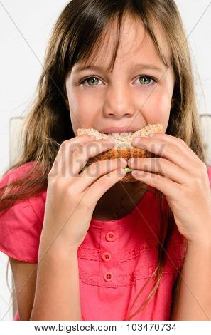 Cute young girl smiling while biting eating her wholemeal sandwich