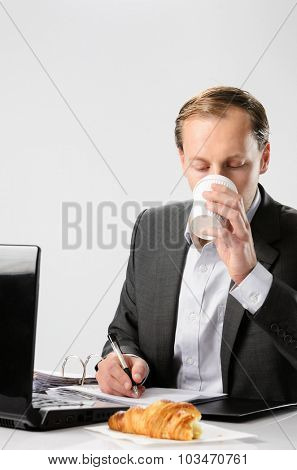 Businessman drinks coffee while working hard signing documents and contracts