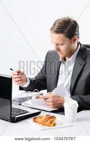 Busy businessman has to sign documents and look over contracts, no time to finish breakfast croissant