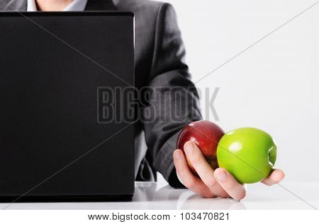 Healthy businessman in suit holds red and green apple while working on his laptop computer, vitality or fresh ideas concept