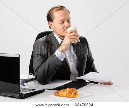 Businessman drinks enjoys his morning coffee and croissant before he starts work