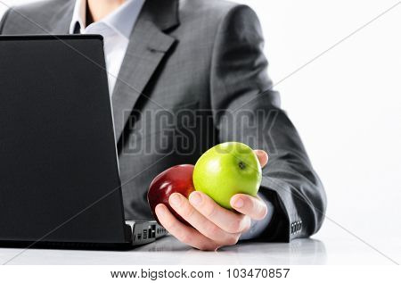 Man in business suit holds bright vibrant red and green apple in hand, symbolising fresh options concepts or healthy lifestyle in the office