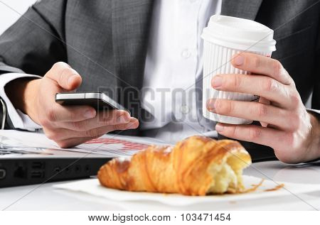 Businessman holds take away coffee cup while working checking emails on his phone with half eaten breakfast croissant in front of him
