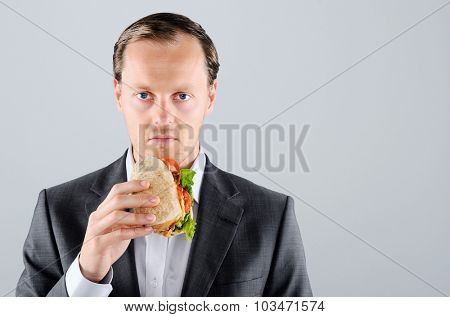 Busy businessman on the move, eating lunch a take away sandwich roll along the way