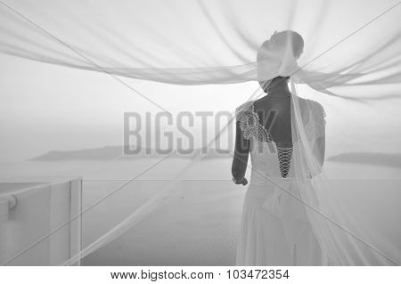 Pretty woman posing in white wedding dress on Santorini island, Greece