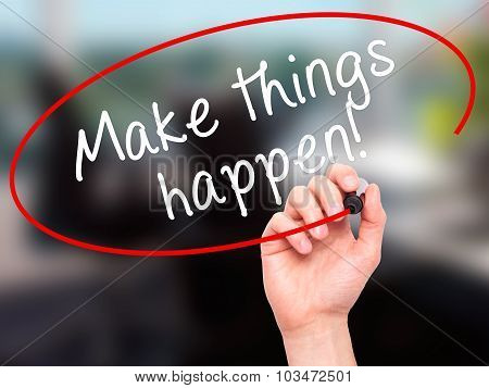 Man Hand writing Make Things Happen with marker on transparent wipe board.