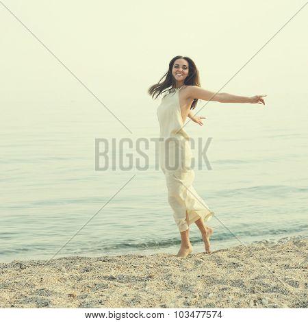 Beautiful happy woman wearing long white dress having fun on a seacoast.