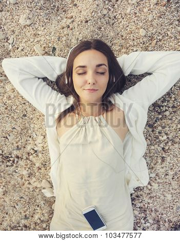 Young smiling woman outdoor portrait lying on a sea sand and listening music, top view.