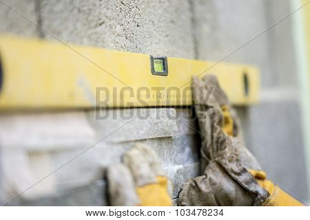 Closeup Of Manual Worker Wearing Protective Gloves Holding A Yellow Label Against A Wall