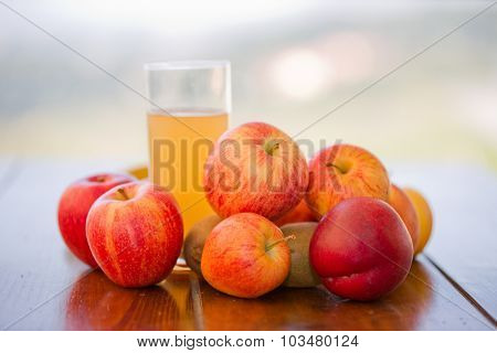 fruits and juice on a wooden table, outdoor