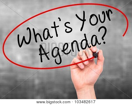 Man Hand writing What's Your Agenda with marker on transparent wipe board.