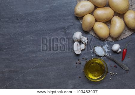 Potatos, Mushrooms And Condiment On Dark Wooden Table