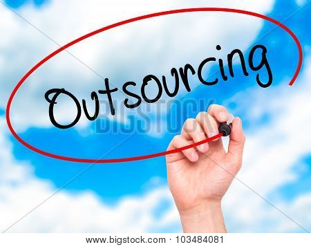 Man Hand writing Outsourcing with marker on transparent wipe board.