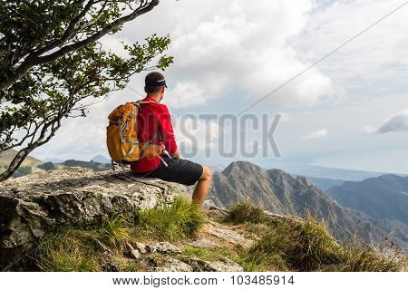 Hiking man climber or trail runner looking at beautiful view in mountains. Travel in Italy Europe. F