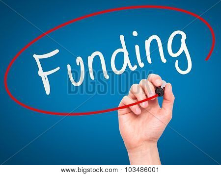 Man Hand writing Funding with marker on transparent wipe board.
