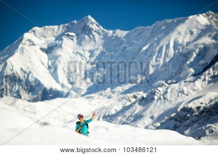 Young happy woman hiker looking at mountain peak summit in winter mountains. Climbing inspiration an