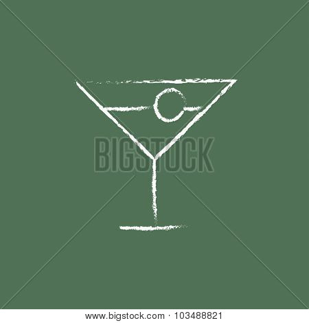 Cocktail glass hand drawn in chalk on a blackboard vector white icon isolated on a green background.