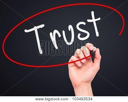 Man Hand writing Trust black marker on visual screen.