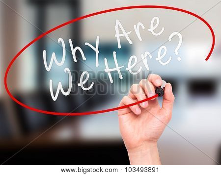 Man Hand writing Why Are We Here black marker on visual screen.