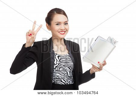 Young Asian Business Woman Show Victor Sign With A Book