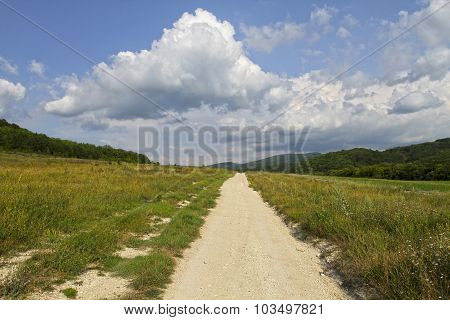 Unpaved Dirt Road Takes To The Sky With Clouds