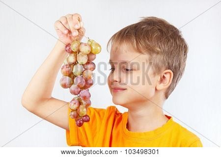 Young boy in orange shirt with a grape
