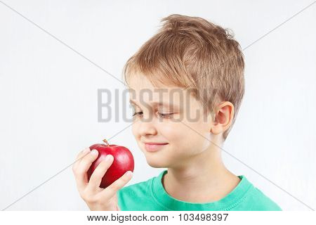 Little boy in green shirt with red apple