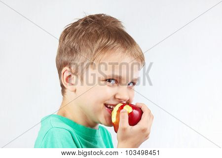 Little funny boy in a green shirt eating red apple