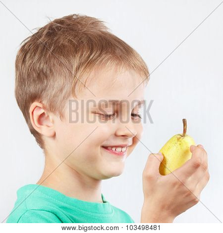 Little boy in green shirt with ripe yellow pear