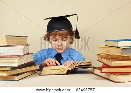 Little serious boy in academic hat studies old books