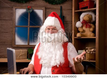 Santa Claus In Workshop With Laptop