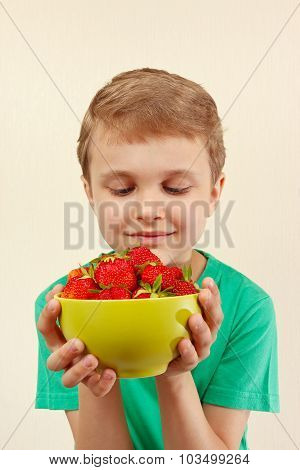 Young boy with bowl of sweet red strawberries