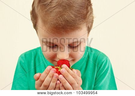Little boy sniffing aroma of fresh strawberries