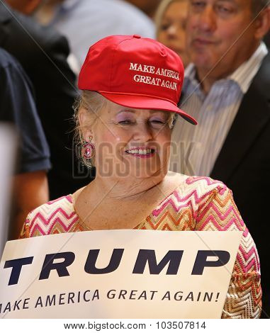 Trump supporter in red had with sign