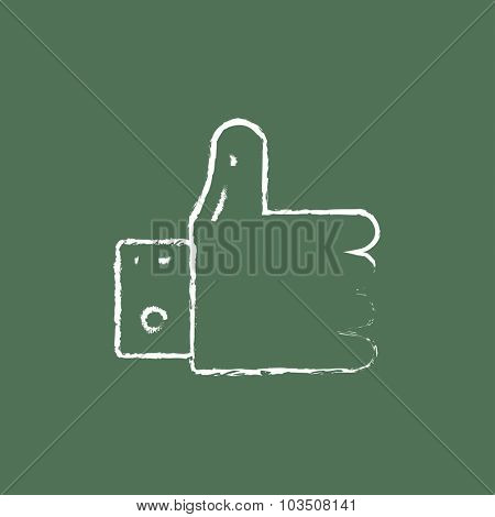 Hand with thumb up hand drawn in chalk on a blackboard vector white icon isolated on a green background.