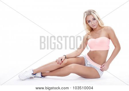 Full-length portrait of a beautiful young adult cheerful blonde woman in sporty outfit isolated on white background