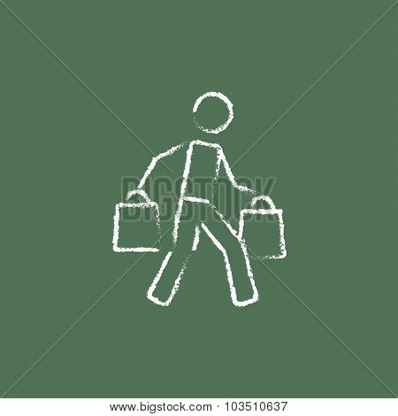 Man carrying shopping bags hand drawn in chalk on a blackboard vector white icon isolated on a green background.