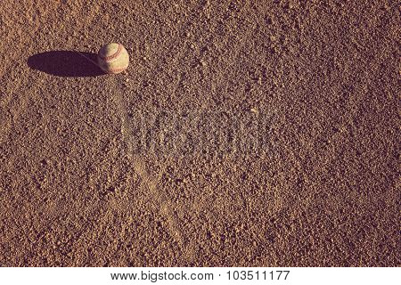 Baseball in the infield with late afternoon shadows